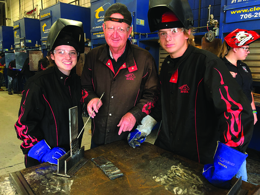 Welding students with their instructor